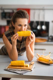Woman biting into corncob while leaning on kitchen counter. Looking off into the distance, a woman is leaning with her elbows on the kitchen counter as she takes stock photo