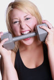 Woman biting dumbbell Stock Image