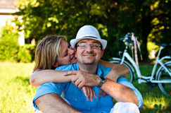 Woman biting ear of man. Flirting, middle aged couple in the park stock photography