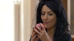 Woman biting and eating a tasty red apple. Young woman biting and eating a tasty red apple stock footage