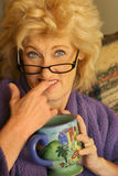Woman biting figner. Funny portrait of older woman biting her finger with comic expression Stock Photos