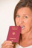 Woman biting German passport Stock Images