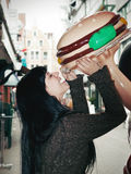 Woman biting into giant burger Royalty Free Stock Photo