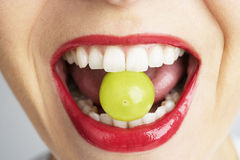 Woman Biting Grape royalty free stock image