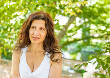 Woman biting her lip with puzzled look. Curvy menopausal woman standing in a park with crossed arms is biting her lip with puzzled look Royalty Free Stock Image