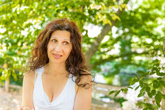 Woman biting her lip with puzzled look. Curvy menopausal woman standing in a park with crossed arms is biting her lip with puzzled look Royalty Free Stock Photos
