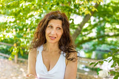 Woman biting her lip with puzzled look. Curvy menopausal woman standing in a park with crossed arms is biting her lip with puzzled look Royalty Free Stock Photo