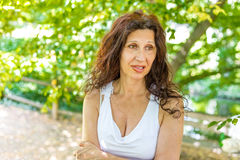 Woman biting her lip with puzzled look. Curvy menopausal woman standing in a park with crossed arms is biting her lip with puzzled look Stock Photo