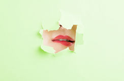 Woman biting her lip thru ripped green paper hole Royalty Free Stock Photos