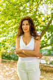 Woman biting her lip with worried look. Curvy menopausal woman standing in a park with crossed arms is biting her lip with worried look Stock Photos