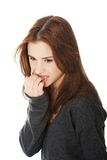Woman biting her nails. Young stressed woman biting her nails Royalty Free Stock Photos