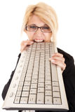 Woman biting keyboard Royalty Free Stock Photo