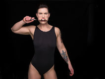 Woman biting knife. Woman wearing black leotard with tattoos biting a kitchen knife against black background royalty free stock photography