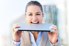 Woman biting a laptop. Young woman biting a laptop Royalty Free Stock Photos