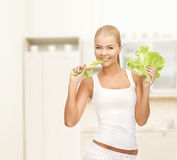 Woman biting lettuce. Diet and fitness concept - picture of healthy woman biting piece of lettuce stock photos