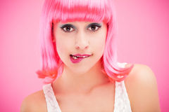 Woman biting lip. Woman wearing wig over pink background Stock Photography