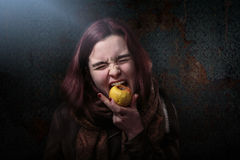 Woman is biting in an old apple. Desperate woman is biting in an old apple royalty free stock images