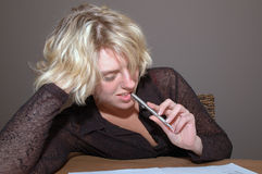 Woman biting pen. Portrait of a young blond woman, biting a pen as she casually reads a book or document Stock Images