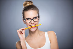 Woman biting a pencil Stock Images