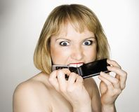 Woman biting phone. Stock Images