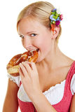 Woman biting in a pretzel. Young bavarian woman in a dirndl biting in a pretzel Royalty Free Stock Photos