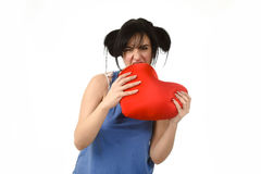 Woman biting in rage spiteful and resentful a red heart shape pillow upset. Young attractive and beautiful woman biting in rage spiteful and resentful a red Royalty Free Stock Photography