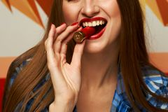 Free Woman Biting Red Shotgun Shell Stock Photography - 117323612
