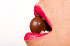 Woman biting a round chocolate ball Royalty Free Stock Image