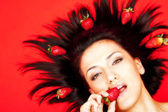 Woman biting strawberry Stock Photo