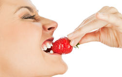 Woman biting strawberry. Profile of a young female biting fresh strawberry, isolated on white royalty free stock photo