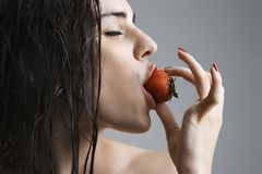 Woman biting strawberry. Stock Photo