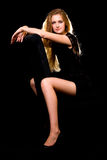 Woman on black. Full body of a beautiful woman with long blond hair and sexy long thin legs wearing black dress posing on black background Royalty Free Stock Images