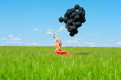 Woman with black balloons running on the green field Royalty Free Stock Photos