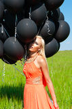 Woman with black balloons Royalty Free Stock Image