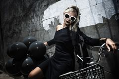 Woman with black baloons. Beautiful young woman with bicycle posing on the street with a lot of black baloons royalty free stock images