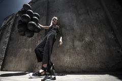 Woman with black baloons. Beautiful young woman posing on the street with a lot of black baloons stock photography