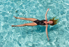 The woman in a black bathing suit swims in the sea Royalty Free Stock Photo