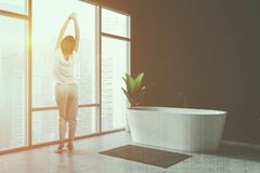 Woman in black bathroom with white tub. Rear view of woman in pajamas standing in minimalistic bathroom interior with black walls, panoramic windows and rug near stock photo