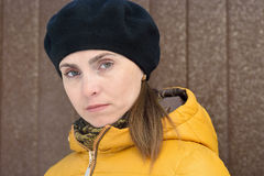 Woman in black beret and a yellow jacket Royalty Free Stock Photography
