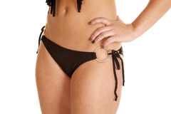 Woman black bikini bottom rings. A woman in her black bikini bottom with her hand on her hip Royalty Free Stock Photos