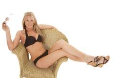 Woman black bikini chair side hold glasses stock image