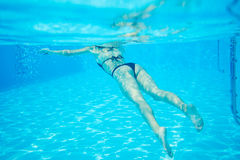Woman in black bikini floating at swimming pool, photo underwater Royalty Free Stock Photo
