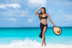 Woman in black bikini and sarong walking on beach. Elegant sexy girl wearing fashion beachwear putting on sunglasses and straw hat for sun uv protection Royalty Free Stock Photography