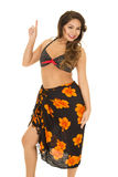 Woman in black bikini top and sarong around waist finger up Royalty Free Stock Image