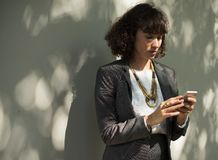 Woman In Black Blazer Holding A Smartphone While Standing Near Wall Stock Photography