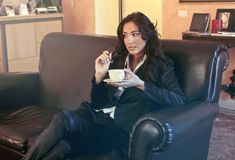Woman in Black Blazer Holding Teacup While Sits on Black Sofa royalty free stock photography