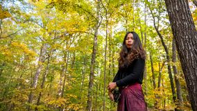 Woman in black blouse and sarong standing in forest stock images
