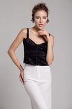 Woman in black blouse and white trousers Royalty Free Stock Photography