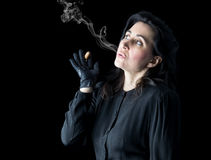 Woman in Black Blowing Cigar Smoke Stock Photo