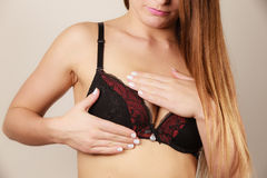 Woman in black bra lingerie taking care of her breasts Royalty Free Stock Photography